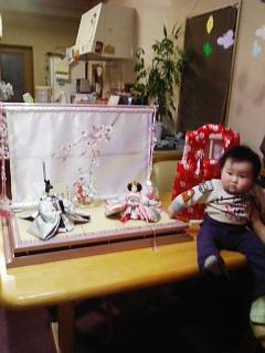 テーブルの上に飾った雛人形の横に赤ちゃんが座ってハイ。ポーズ。