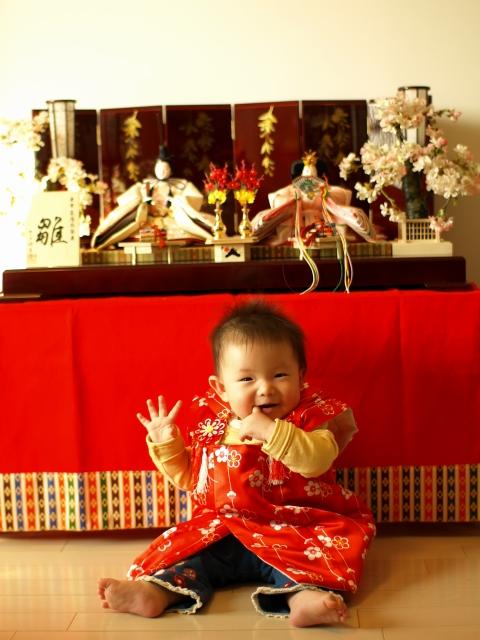 テーブルの上に飾った雛人形の前に座った笑顔の赤ちゃん。