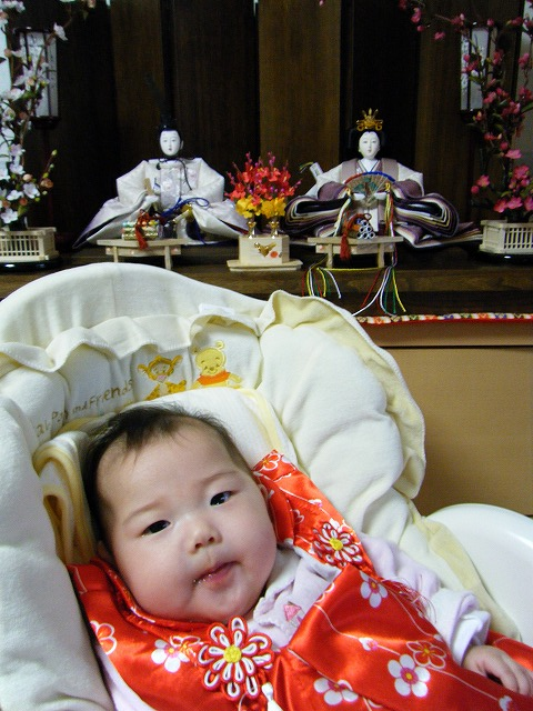雛人形の前でこっちを向いている赤ちゃん。