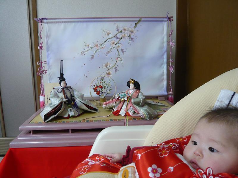 雛人形の前で椅子に寝そべった赤ちゃん。