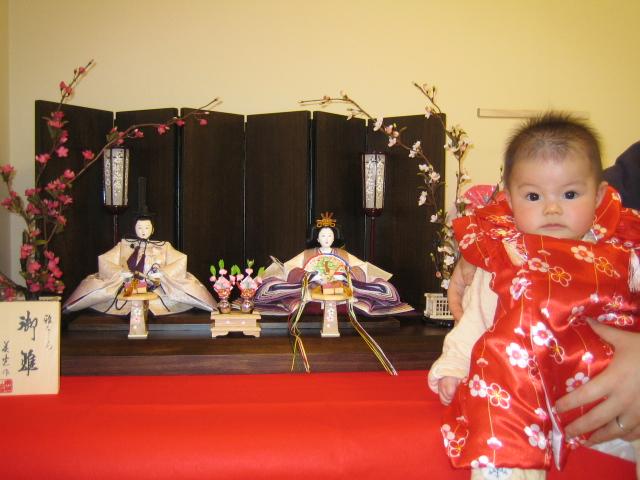 抱っこされた赤ちゃんと雛人形の記念写真です。
