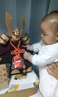 男の子の赤ちゃんが五月人形の兜をいじくっています。